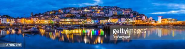 brixham fishing village warmly illuminated at dusk panorama devon uk - torquay,_victoria stock pictures, royalty-free photos & images
