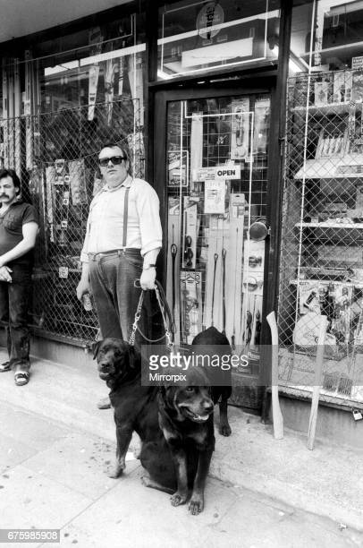 A Brixton shopkeeper prepares to defend his stock against looters with dogs shortly after the riots 12th July 1981