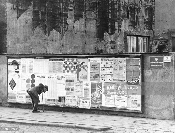 Brno Czechoslovakia man bending down to read a poster in the Gottwaldova street