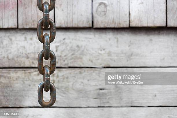 Broad Metal Anchor Chain Against Wood Panel