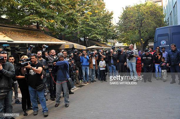 TV broadcast and photoreporters wait outside the courthouse on October 21 in the central Greek city of of Larissa where a Roma couple is due to...