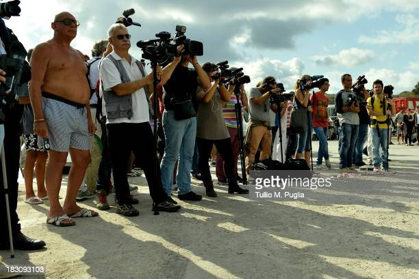 Broadcast crew work at the Lampedusa port on October 4 2013 in Lampedusa Italy The search for bodies continues off the coast of Southern Italy as the...