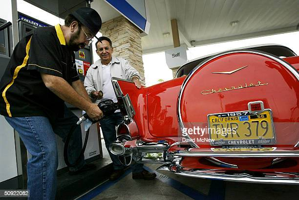 Broadcast entertainer 'Shotgun Tom' Kelly pumps 35centpergallon gas into a 1957 Chevrolet owned by Ray Luna on June 3 2004 in Cypress California...