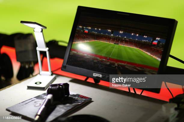 Broadcast microphone is seen alongside a match day programme that has the message No Room For Racism on prior to the Premier League match between...