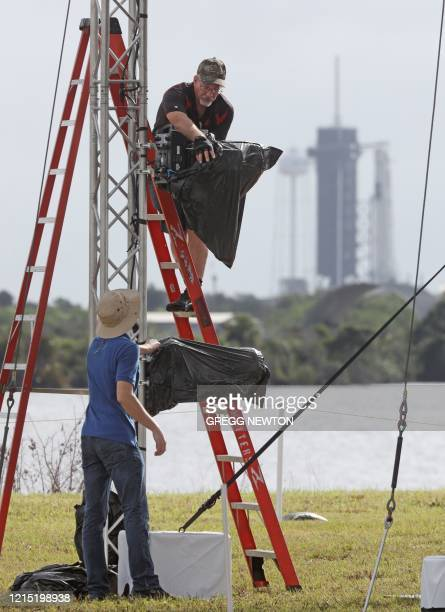 NASA broadcast technicians make preparations for coverage at the Kennedy Space Center in Florida on May 26 2020 Looming in the distance is the SpaceX...