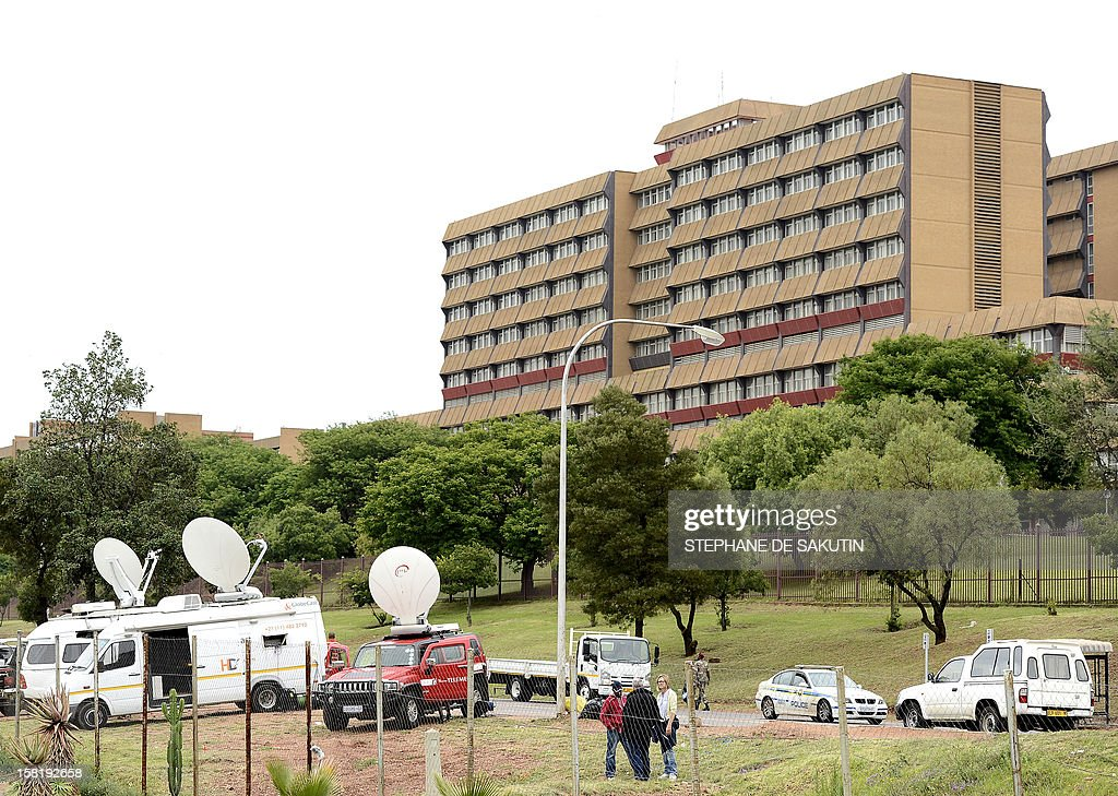 Broadcast vans are parked near the 1 Military Hospital (R) where South Africa's former President Nelson Mandela is hospitalised on December 11, 2012 in Pretoria. Nelson Mandela has a lung infection but is responding to treatment, the South African government said today, as the revered anti-apartheid icon spent his fourth day in hospital.