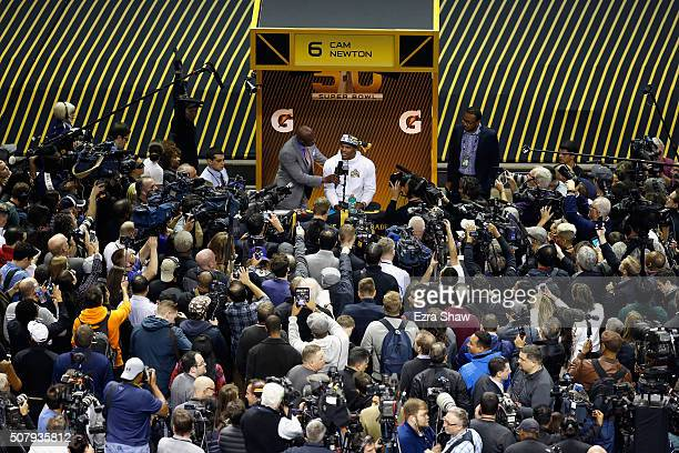NFL broadcaster Deion Sanders interviews Cam Newton of the Carolina Panthers at Super Bowl Opening Night Fueled by Gatorade at SAP Center on February...