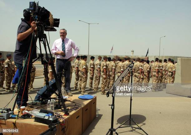 Broadcaster Huw Edwards faces the camera as soldiers march past prior to a memorial service held at the Contingency Operating Base and attended by...