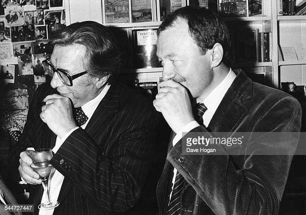 Broadcaster Robin Day and politician Ken Livingstone both with their hands to their face as they make a tennis elbow joke circa 1988