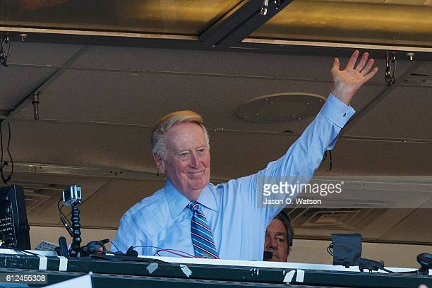 Broadcaster Vin Scully waves to the crowd during the seventh inning between the San Francisco Giants and the Los Angeles Dodgers at ATT Park on...