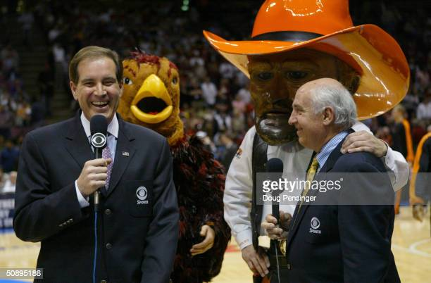CBS broadcasters Jim Nantz and Billy Packer stand in front of the St Joseph's Hawks mascot and the Oklahoma State Cowboys mascot before the Elite 8...