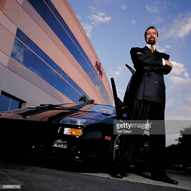 Broadcom CEO Henry T Nicholas III stands next to his Lamborghini Diabl outside the company's headquarters