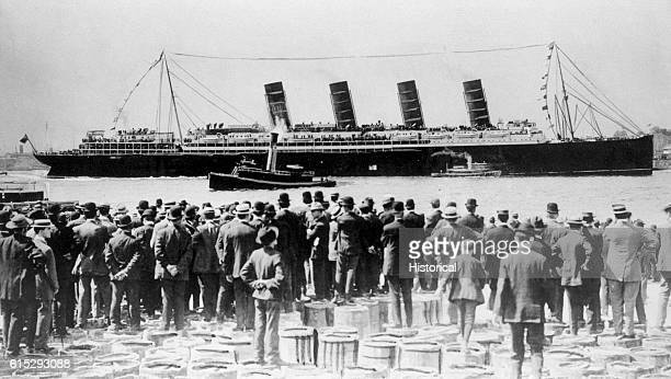 Broadside view of the passenger ship Lusitania after her maiden voyage Viewers watch from a pier The Lusitania was sunk by a German submarine in...