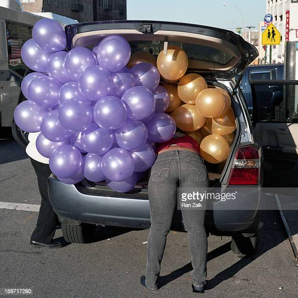 Broadway and 183rd Manhattan. Party accessory store worker loading colored balloons in a back of a van and falling in.