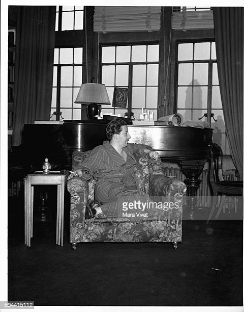 Broadway producer and songwriter Billy Rose relaxes in an arm chair inside a high rise apartment