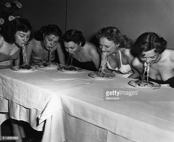 Broadway showgirls Geraldine Shay Pat Gale Bonnie Blair Genne Courtney and Toni Tucci eat spaghetti with their arms held behind their backs as part...