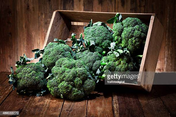 Broccoli in a crate on rustic wood table