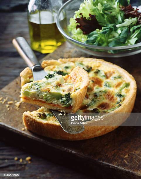 Broccoli quiche and salad leaves on wooden chopping board