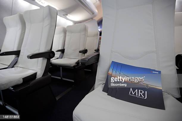 Brochures for Mitsubishi Aircraft Corp's Mitsubishi Regional Jet sit on a seat inside a mockup cabin of the company's aircraft on on the third day of...