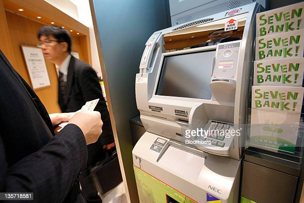 Brochures for Seven Bank Ltd sit next to an automated teller machine at a branch in Tokyo Japan on Tuesday Dec 13 2011 Shareholders in Seven Bank Ltd...