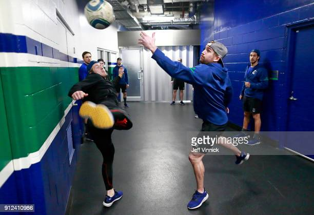 Brock Boeser and Sven Baertschi of the Vancouver Canucks reach for a soccer ball before their NHL game against the Colorado Avalanche at Rogers Arena...