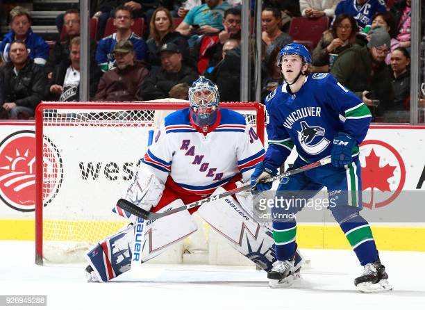 Brock Boeser of the Vancouver Canucks and Henrik Lundqvist of the New York Rangers watch the puck during their NHL game at Rogers Arena February 28...