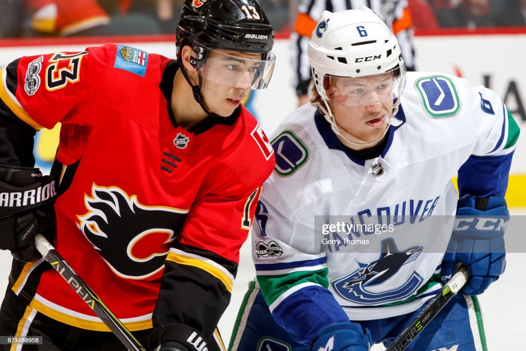 Brock Boeser #6 of the Vancouver Canucks and Johnny Gaudreau #13 of the Calgary Flames in an NHL game against the Vancouver Canucks at the Scotiabank Saddledome on November 7, 2017 in Calgary, Alberta, Canada.