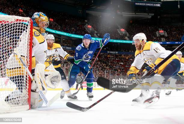 Brock Boeser of the Vancouver Canucks chases Mattias Ekholm of the Nashville Predators for a loose puck during their NHL game at Rogers Arena...