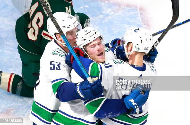 Brock Boeser of the Vancouver Canucks is congratulated by teammates Bo Horvat and Elias Pettersson after he scored a goal in the second period...