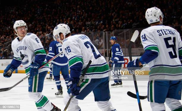 Brock Boeser of the Vancouver Canucks leads his teammates Thomas Vanek and Troy Stecher to the bench after scoring on the Toronto Maple Leafs during...