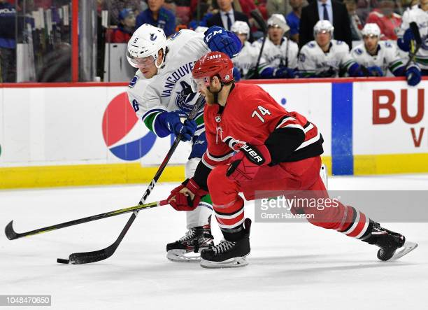 Brock Boeser of the Vancouver Canucks takes a shot against Jaccob Slavin of the Carolina Hurricanes during their game at PNC Arena on October 9, 2018...
