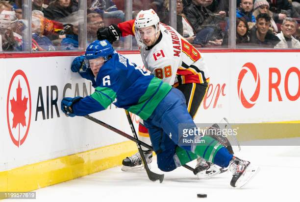 Brock Boeser of the Vancouver Canucks gets checked into the end boards while battling for the loose puck against Andrew Mangiapane of the Calgary...