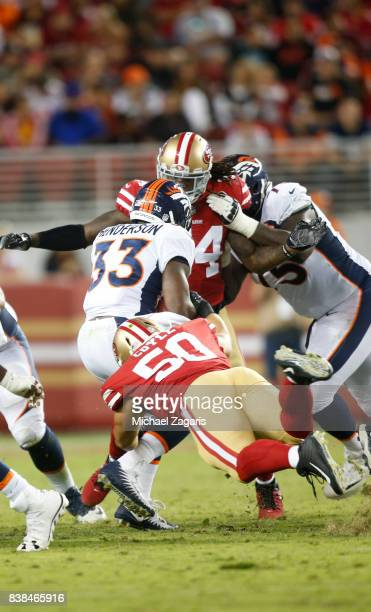 Brock Coyle and Arik Armstead of the San Francisco 49ers tackle De'Angelo Henderson of the Denver Broncos during the game at at Levi Stadium on...