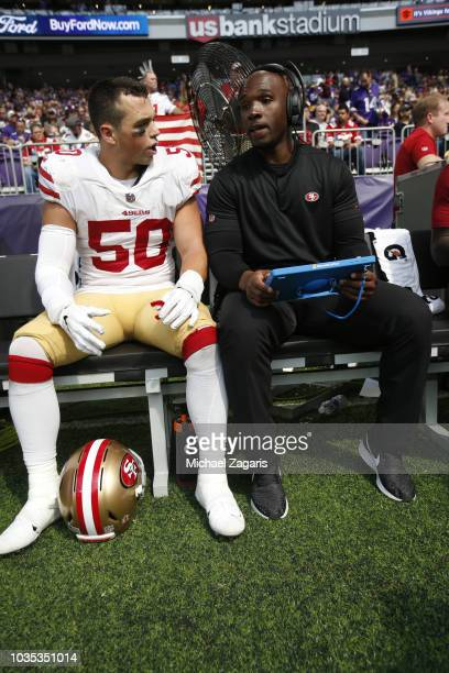 Brock Coyle and Inside Linebackers Coach DeMeco Ryans of the San Francisco 49ers talk on the bench during the game against the Minnesota Vikings at...