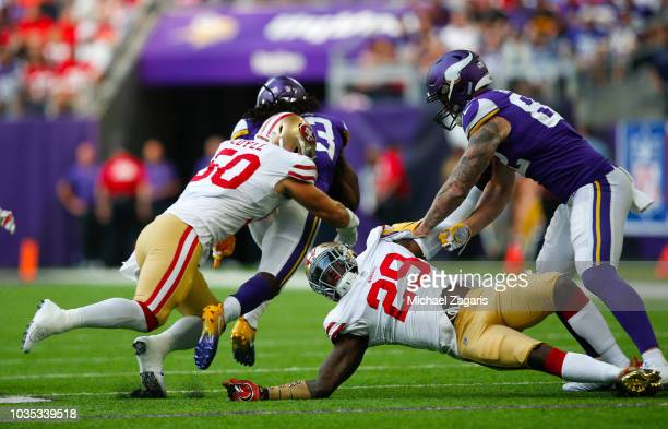 Brock Coyle and Jaquiski Tartt of the San Francisco 49ers tackle Dalvin Cook 333 of the Minnesota Vikings during the game at U.S. Bank Stadium on...