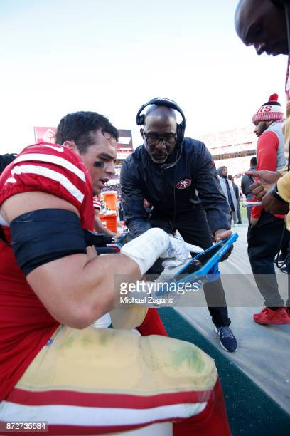 Brock Coyle and Linebackers Coach Johnny Holland of the San Francisco 49ers talk on the sideline during the game against the Arizona Cardinals at...