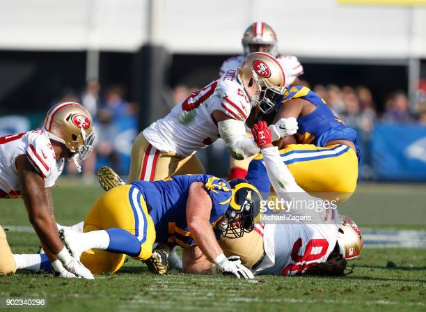 Brock Coyle and Sheldon Day of the San Francisco 49ers tackle Malcolm Brown of the Los Angeles Rams during the game at Los Angeles Memorial Coliseum...