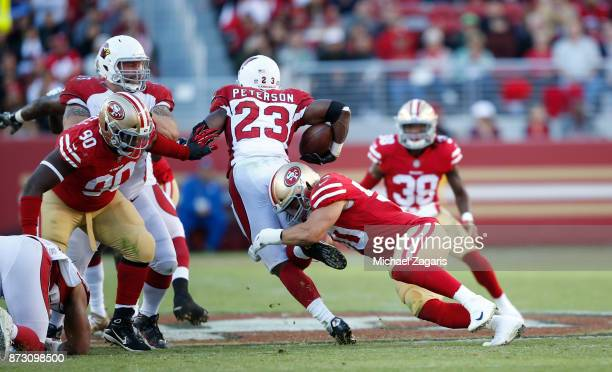 Brock Coyle of the San Francisco 49ers tackles Adrian Peterson of the Arizona Cardinals during the game at Levi's Stadium on November 5, 2017 in...