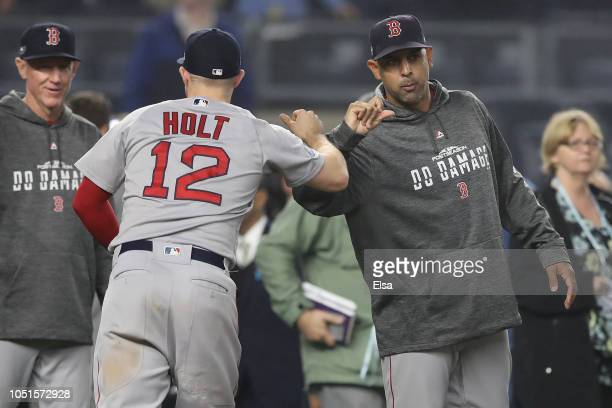 Brock Holt and manager Alex Cora of the Boston Red Sox celebrate after defeating the New York Yankees in Game Three of the American League Division...