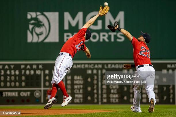 Brock Holt collides with Michael Chavis of the Boston Red Sox as he catches a fly ball during the eighth inning of a game against the Tampa Bay Rays...