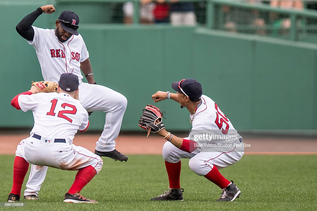 Brock Holt #12, Jackie Bradley Jr. #25, and Mookie Betts #50 of the Boston Red Sox celebrate a victory against the Tampa Bay Rays on August 31, 2016 at Fenway Park in Boston, Massachusetts.