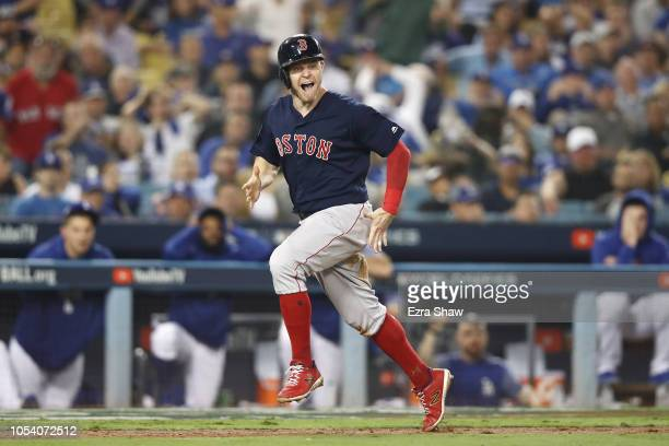 Brock Holt of the Boston Red Sox celebrates as he scores a thirteenth inning run against the Los Angeles Dodgers in Game Three of the 2018 World...