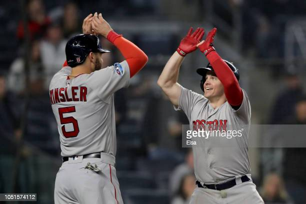 Brock Holt of the Boston Red Sox celebrates with teammate Ian Kinsler after hitting a two run home run against Austin Romine of the New York Yankees...