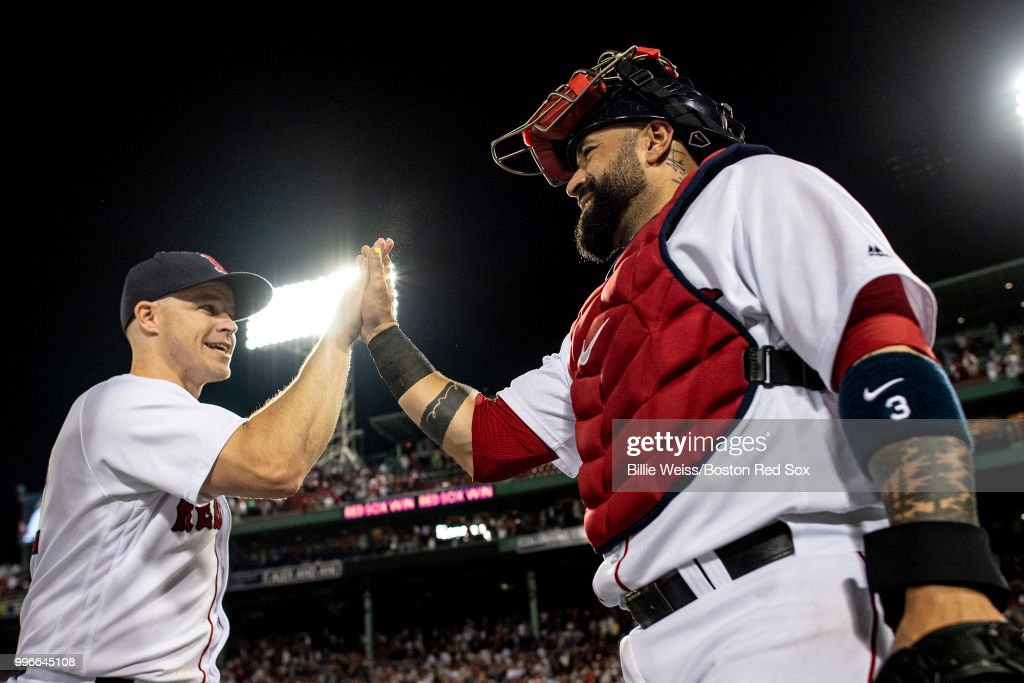 Brock Holt #12 of the Boston Red Sox high fives Sandy Leon #3 after a game against the Texas Rangers on July 11, 2018 at Fenway Park in Boston, Massachusetts.