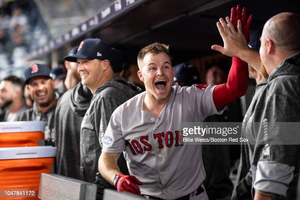 Brock Holt of the Boston Red Sox high fives teammates after hitting a home run during the inning of game three of the American League Division Series...
