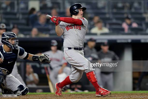 Brock Holt of the Boston Red Sox hits an RBI double to score Rafael Devers against the New York Yankees during the eighth inning in Game Three of the...