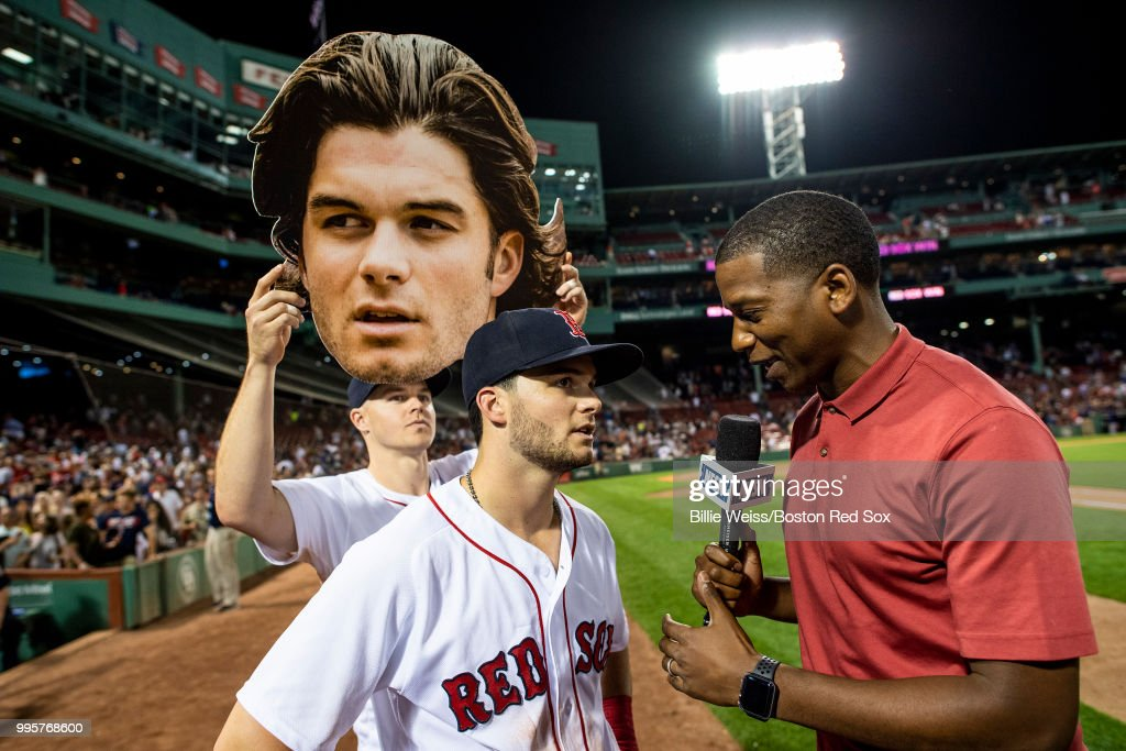 Brock Holt #12 of the Boston Red Sox holds up a big-head cutout of Andrew Benintendi #16 as he is interview by Jahmai Webster of NESN after a game against the Texas Rangers on July 10, 2018 at Fenway Park in Boston, Massachusetts.