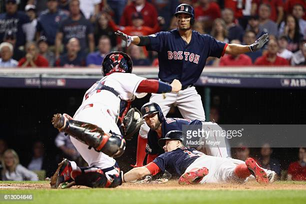 Brock Holt of the Boston Red Sox is called out at home plate after Dustin Pedroia scored a run in the first inning against the Cleveland Indians...