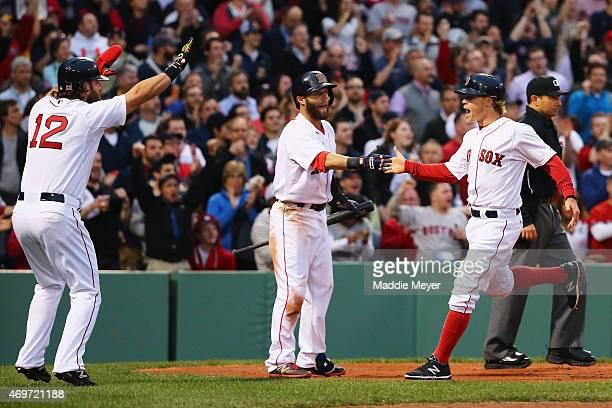 Brock Holt of the Boston Red Sox is celebrates with his teammates Mike Napoli and Dustin Pedroia after scoring a run against the Washington Nationals...