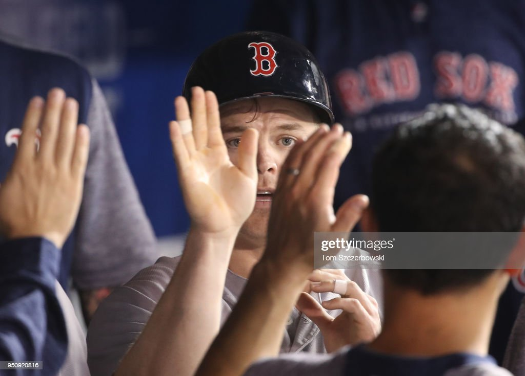 Brock Holt #12 of the Boston Red Sox is congratulated by teammates in the dugout after scoring a run in the sixth inning during MLB game action against the Toronto Blue Jays at Rogers Centre on April 24, 2018 in Toronto, Canada.